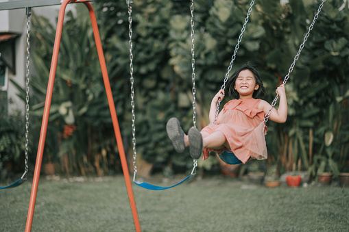 asian chinese Child playing on swing