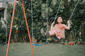 istock asian chinese Child young girl playing on swing staycation 1280199408