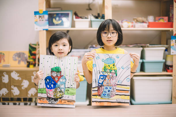 2 asian chinese children displaying their painting after the class at the art center looking at the camera stock photo