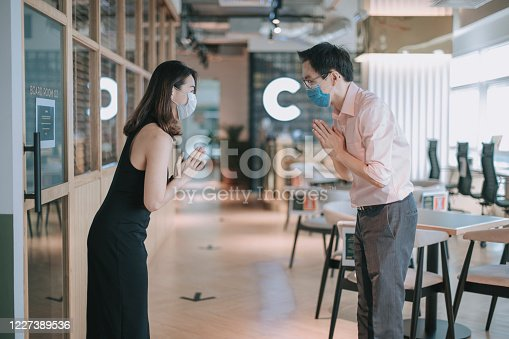 2 asian chinese colleague greeting on each other with new handshake style in office with protective mask on