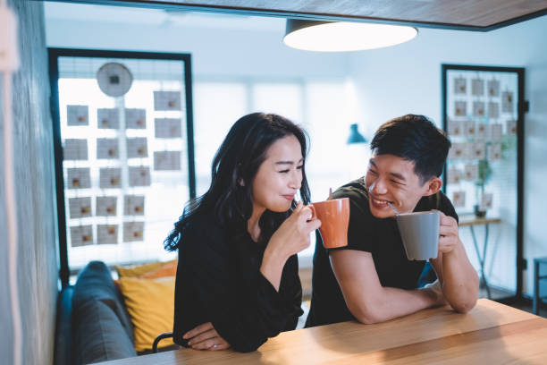 asian chinese couple at the dining chatting bonding time while having their coffee in the morning stock photo