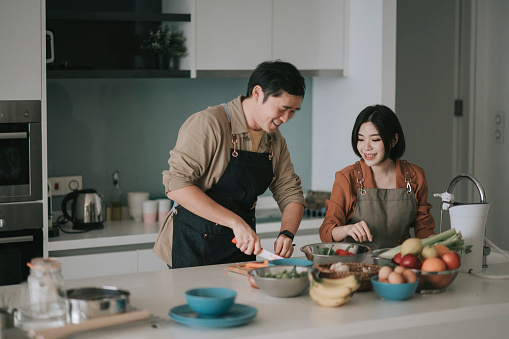 asian chinese couple preparing ingredients cooking meals for family at kitchen counter