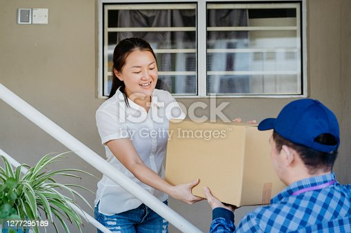 Asian Chinese delivery man holding a carton and delivering to the house of an online shopping customer