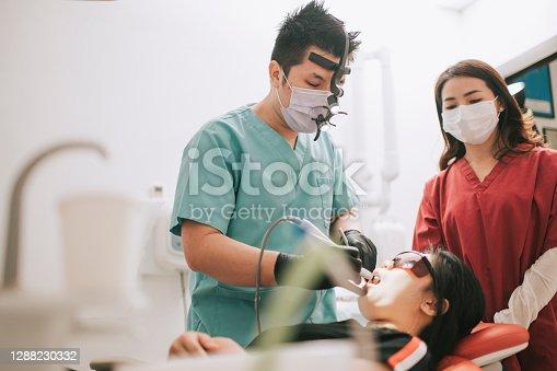 istock asian chinese dentist installing Dental prosthetist tool implant 1288230332