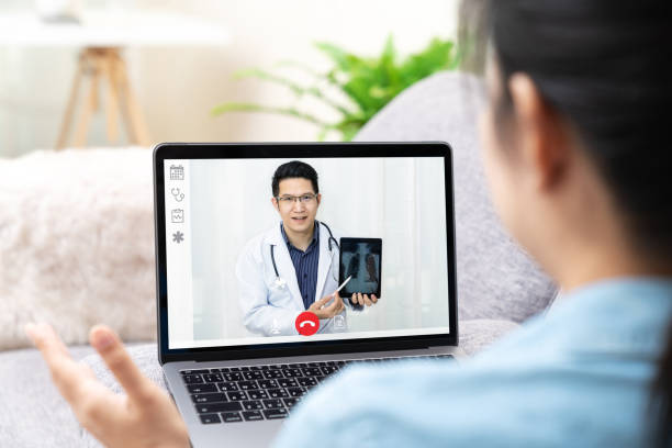 Asian chinese doctor video conference call online talking for follow up remotely with medical coronavirus result at home. Online healthcare digital technology service, counselor and internet support. stock photo