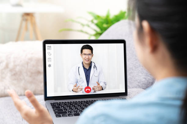 Asian chinese doctor video conference call online talking for follow up remotely with medical coronavirus result at home.Online healthcare digital technology service, counselor and interview app. stock photo