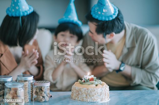 asian chinese family at home celebrating birthday with son wearing party hat wishing in front of birthday cake