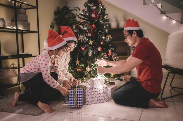 asiatische chinesische familie schmücken weihnachtsbaum und verpackung weihnachtsgeschenk zu hause immer bereit für die weihnachtsfeier - number 13 stock-fotos und bilder