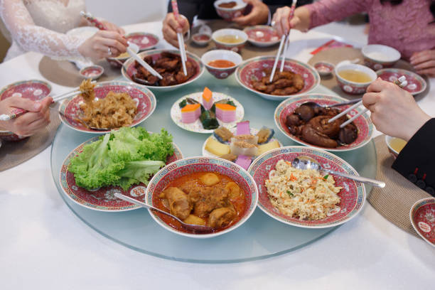 Asian Chinese family enjoy their home made food during wedding ceremony Celebrating Chinese wedding with all traditional local dishes chinese wedding dinner stock pictures, royalty-free photos & images