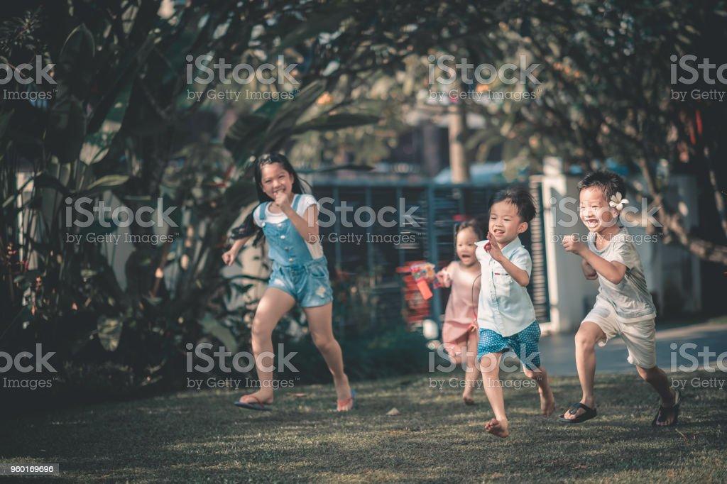 asian chinese family having fun bonding time in front of their house where children running towards parents asian chinese family having fun bonding time in front of their house where children running towards parents Beautiful People Stock Photo