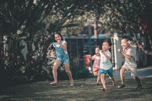 Asian Chinese Family Having Fun Bonding Time In Front Of Their House Where Children Running Towards Parents Stock Photo - Download Image Now