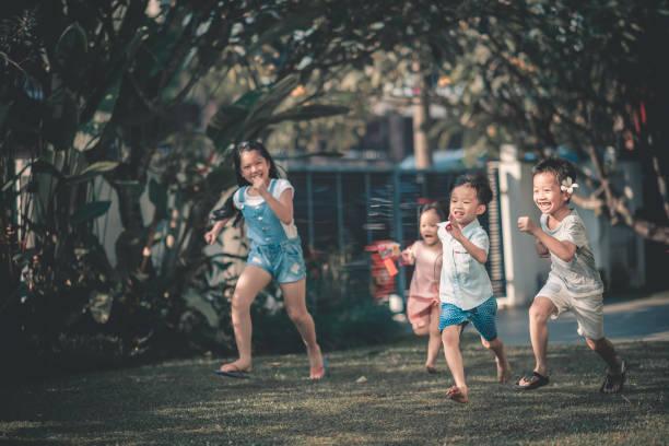 família asiática chinesa, divertir-se tempo em frente à sua casa de ligação onde crianças correndo em direção a pais - malásia - fotografias e filmes do acervo