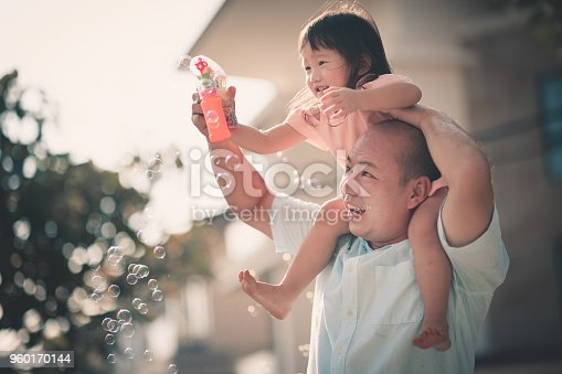 asian chinese family having fun bonding time in front of their house father having daughter over his shoulder