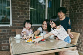 Asian chinese family having teatime with grandmother