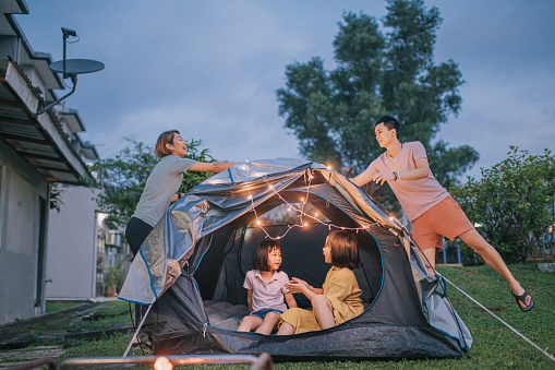 Asian chinese family putting on string light decorating camping at backyard of their house staycation weekend activities