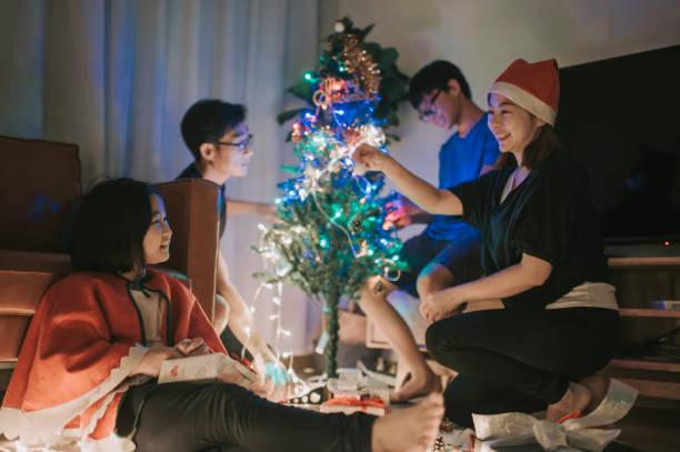 asiatische chinesische familie mit 2 kindern schmücken den weihnachtsbaum im wohnzimmer verbringen zeit zusammen spaß - number 13 stock-fotos und bilder