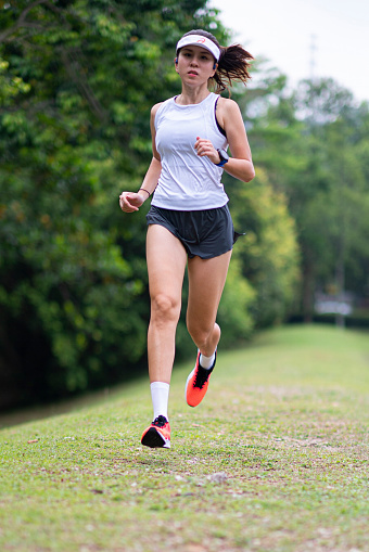 asian chinese female athlete running warm up exercise at public park