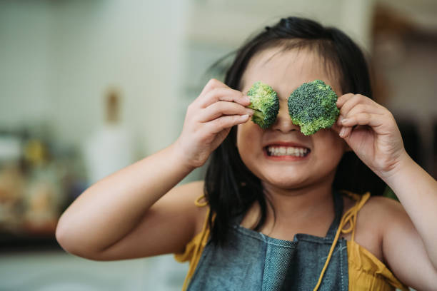 Asian chinese female child act cute with hand holding broccoli putting in front of her eyes with smiling face at kitchen Happiness preparing dinner at kitchen one girl only stock pictures, royalty-free photos & images