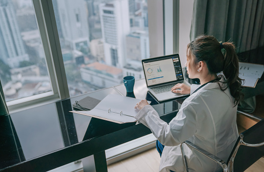asian chinese female doctor working on medical report with laptop and document file
