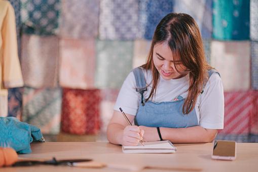 asian chinese female fashion designer drawing traditional clothing batik baju kurung at studio workplace