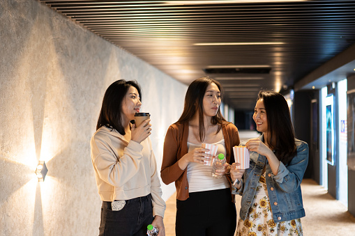 Asian Chinese female friends eating and gossip while walking in corridor going for movie show during weekend