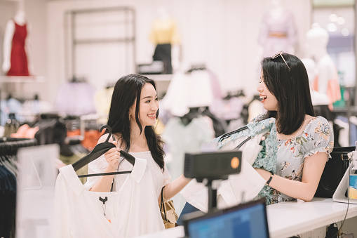 2 asian chinese female friends queuing in front of cashier of clothing store for payment buying dress at the clothe store shopping