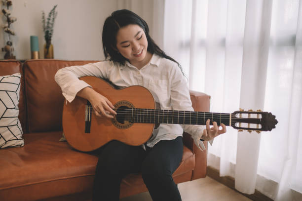 1 asian chinese female playing guitar in living room on sofa stock photo