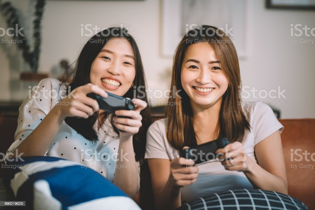2 asian chinese female playing tv games facing camera smiling and holding joystick stock photo