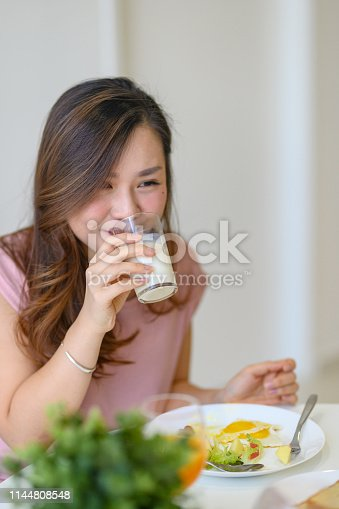 2 asian chinese female sister having breakfast at dining room near window during weekend and having bonding time