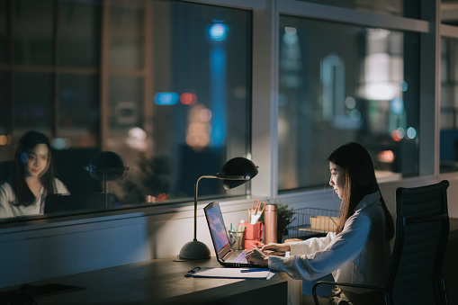 asian chinese female white collar worker working late in office alone at night rushing for financial report