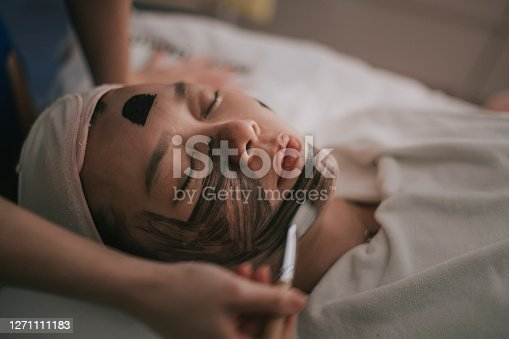 asian chinese female with carbon application on her face in facial spa beauty treatment lying down on bed