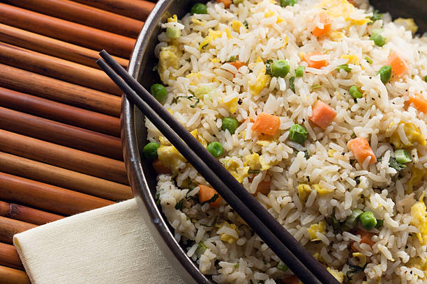 Asian Chinese Fried Rice with Vegetable and Egg with Chopsticks Subject: Traditional authentic Chinese Fried rice served in a bowl. fried rice stock pictures, royalty-free photos & images