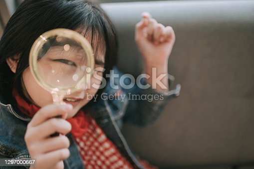 asian chinese girl looking through magnify glass with funny face