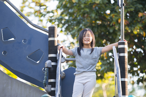Asian Chinese girl playing in children playground in morning