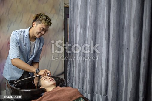 Asian Chinese hairdresser washing customer hair with smiling face in beauty salon.