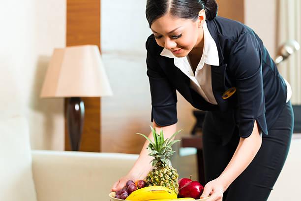 asian chinese hotel housekeeper placing fruit - promi zuhause stock-fotos und bilder