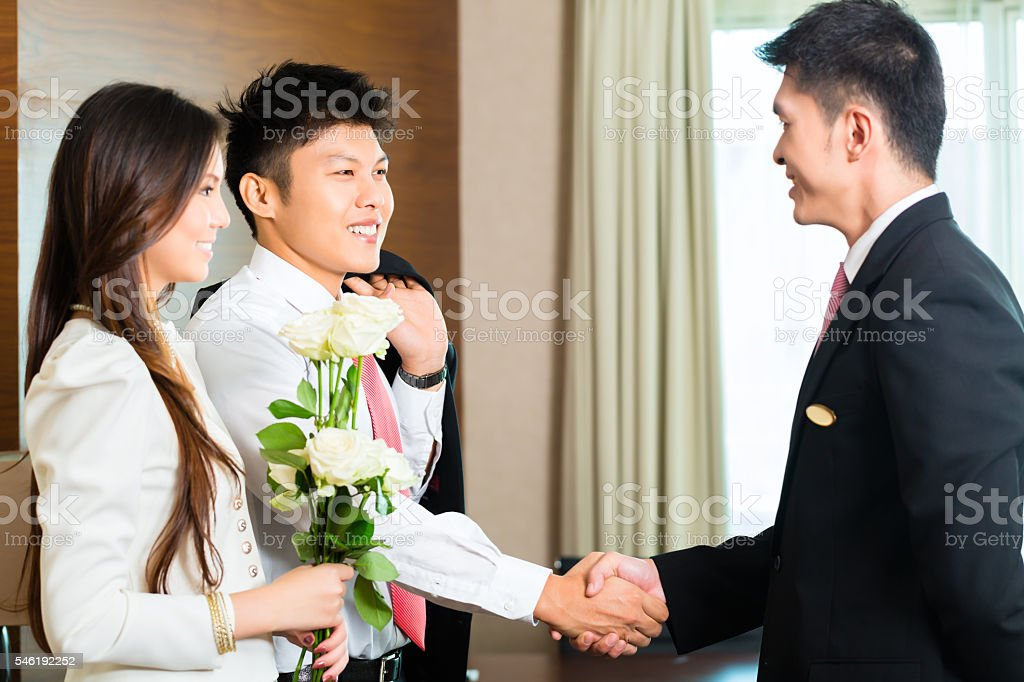 Asian Chinese hotel manager welcoming VIP guest stock photo