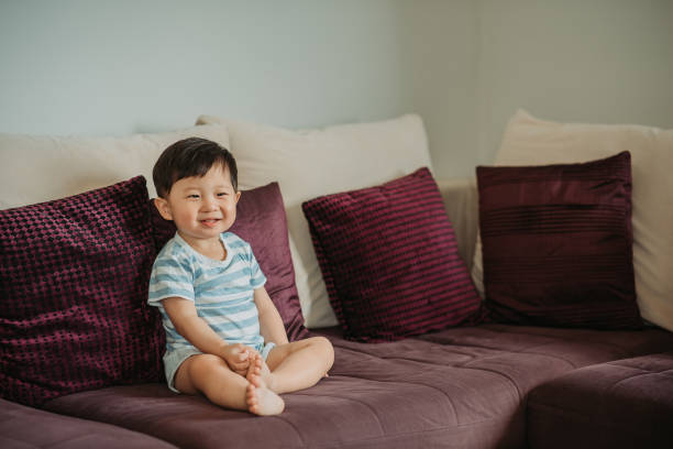 Asian chinese little boy sitting on the sofa with smiling face in a living room Smiling face when watching TV asian little boy stock pictures, royalty-free photos & images