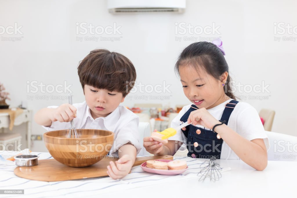Asian Chinese little brother and sister preparing to bake cookies stock photo