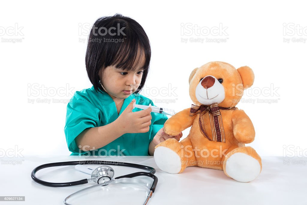 Asian Chinese little doctor girl giving injection to teddy bear stock photo