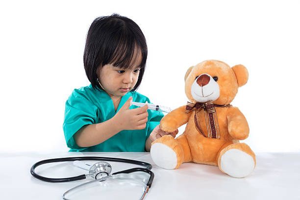 asian chinese little doctor girl giving injection to teddy bear - doktorspiele stock-fotos und bilder