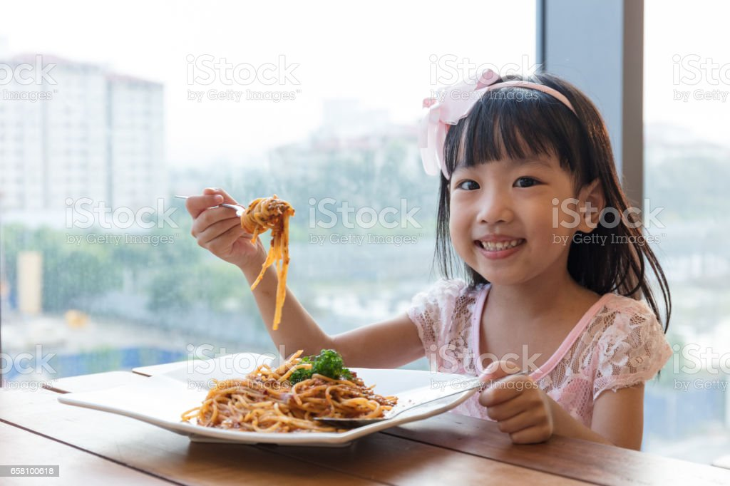 Asian Chinese little girl eating spaghetti bolognese royalty-free stock photo