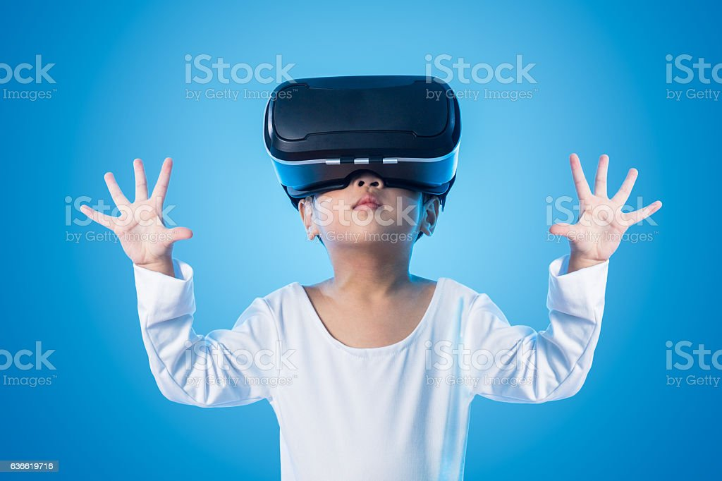 Asian Chinese little girl experiencing virtual reality eyeglasss stock photo