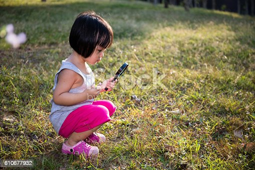 istock Asian Chinese Little Girl Exploring With Magnifying Glass 610677932