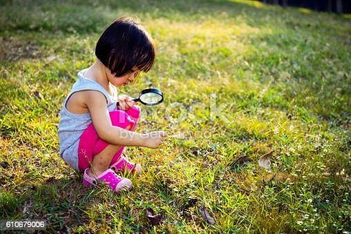 istock Asian Chinese Little Girl Exploring With Magnifying Glass 610679006