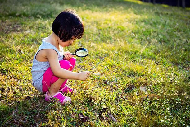 asian chinese little girl exploring with magnifying glass - interessiert stock-fotos und bilder