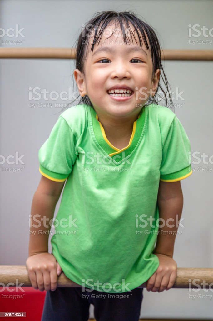 Asian Chinese little girl hanging on uneven bars stock photo