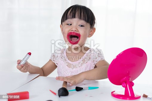 istock Asian Chinese little girl having fun with mess lipstick 659791938
