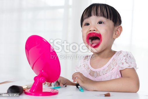 istock Asian Chinese little girl having fun with mess lipstick 659791954