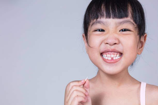 asian chinese little girl holding her missing tooth - criança perdida imagens e fotografias de stock